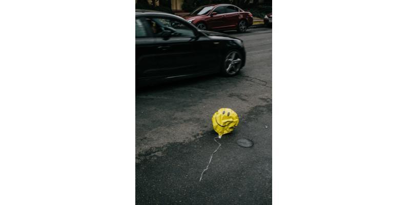 ballon hélium en forme de smiley dégonflé au milieu d'une rue